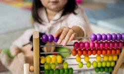 Dodatkowy zasiłek opiekuńczy wydłużony. Dziewczynka w przedszkolu bawiąca się kolorowym liczydłem